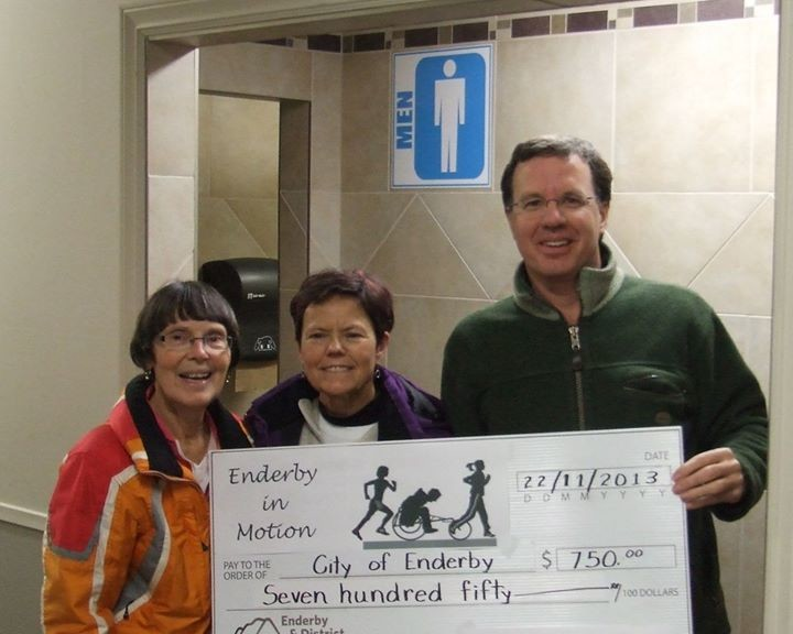 Enderby in Motion representatives present a cheque to Councillor Case for $750 towards accessibility improvements to the Enderby Arena washrooms.