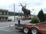 Majestic Metal Art's deer sculpture suspended in mid-air by Central Hardware's crane during installation in Enderby BC
