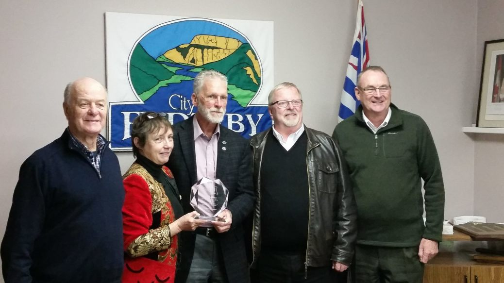 Rick Fairbairn, Rhona Martin, Eric Foster, and Colin Mayes present Earl Shipmaker with an award for 35 years of local government service.